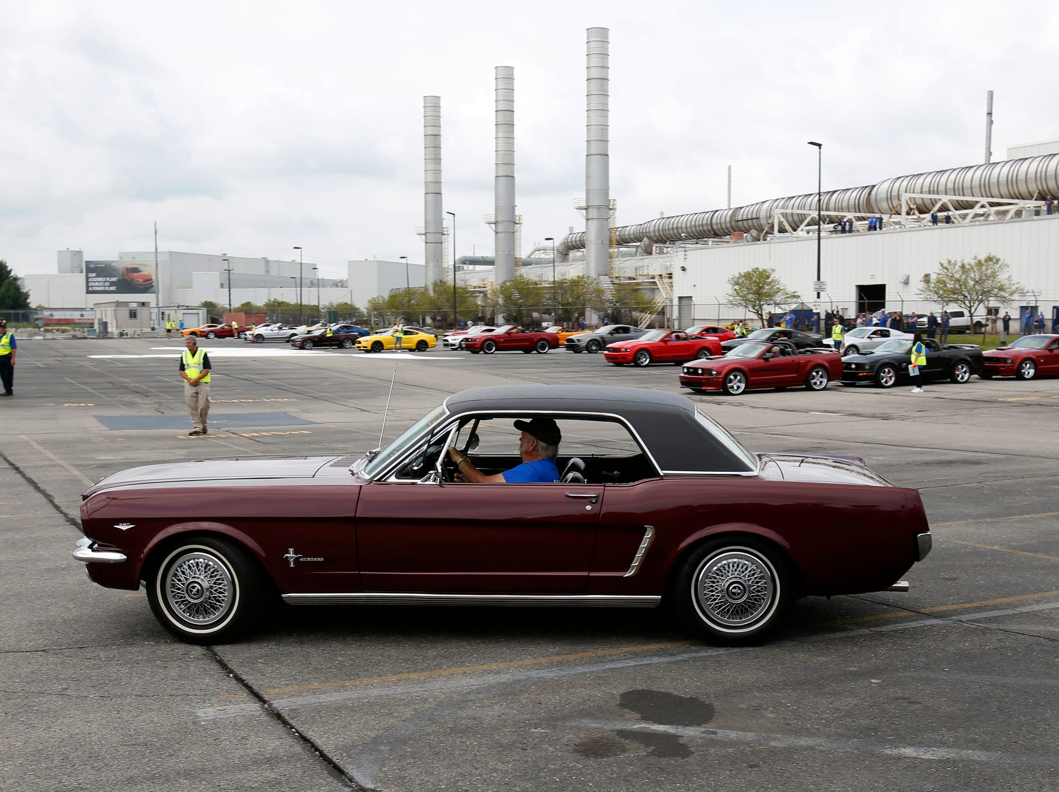 A 1964.5 Ford Mustang makes its way across the parking lot to start the formation of the number 10 million during the celebration of the 10 millionth Mustang at the Ford Motor Company Flat Rock Assembly Plant in Flat Rock on Wednesday, August 8, 2018