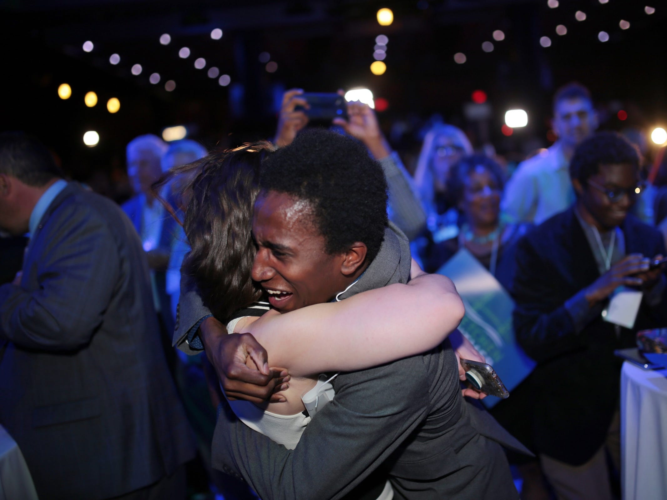 Amanda Dietlin of Rochester and TyJuan Thirdgill of Muskegon, hug after the announcement of democratic gubernatorial candidate Gretchen Whitmer winning during Michigan's primary race on Tuesday, August 7, 2018 at the election night party at the MotorCity Casino in Detroit.