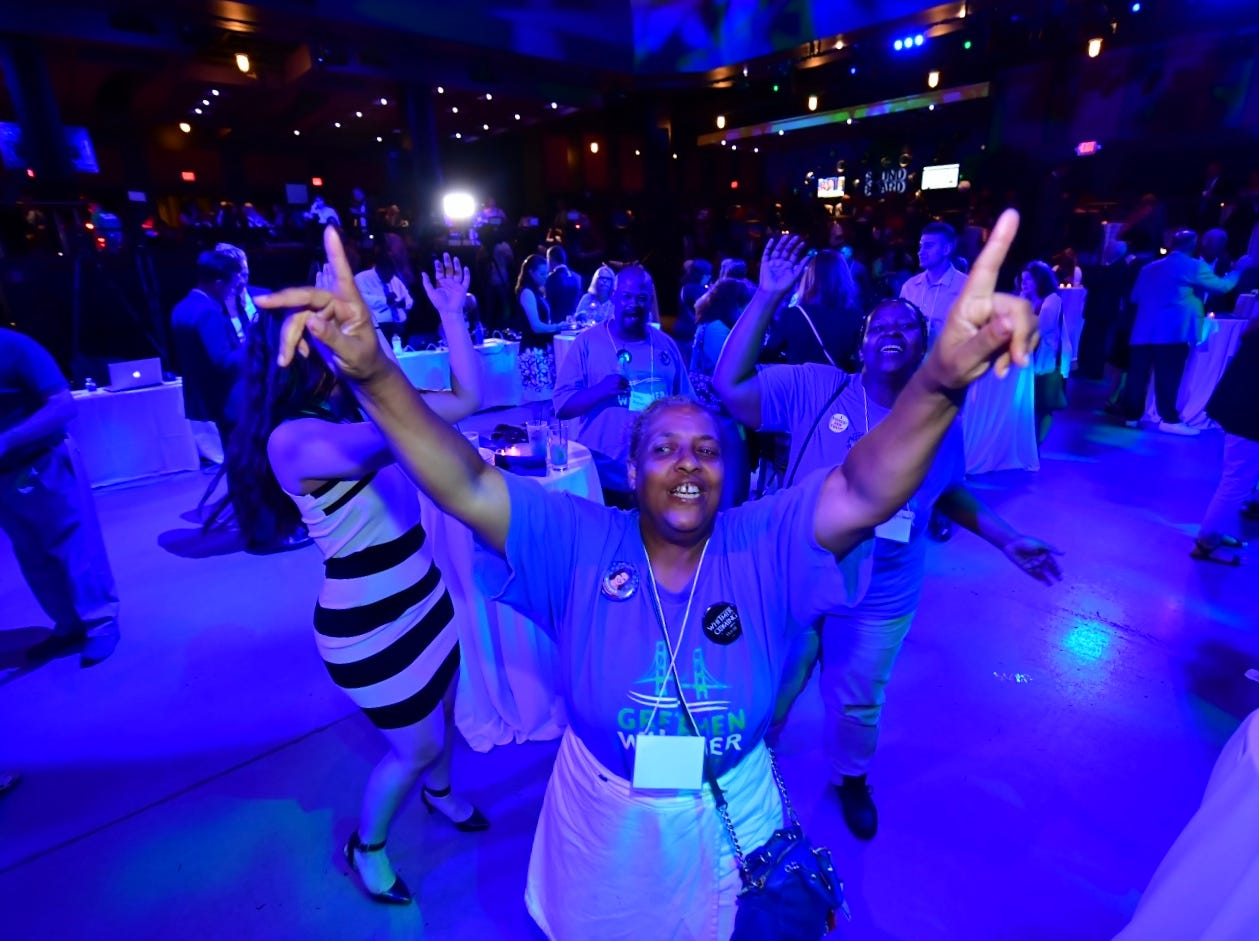 Omega Whigham, of Detroit, dances and sings in support of Gretchen Whitmer during Whitmer's election night party.