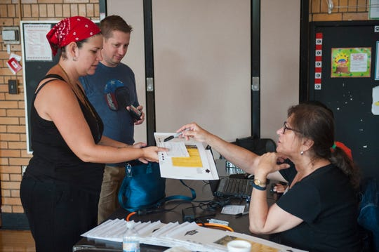 Elisa Gurule and Chris D'Angelo, both of Grosse Pointe Park, get their primary election ballots from election inspector Ann Baxter at Trombly School in Grosse Pointe Park on Tuesday