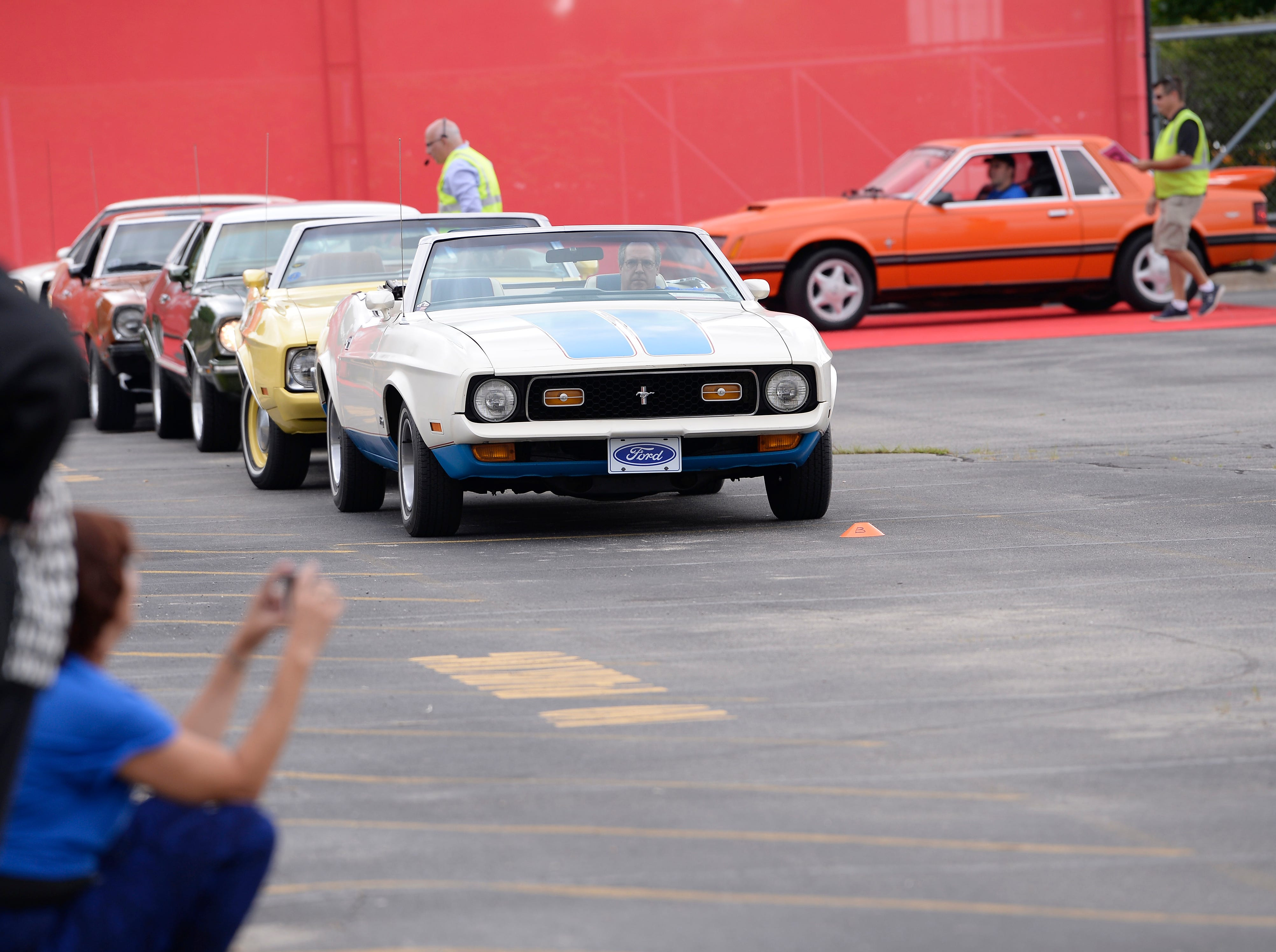 A 1972 Mustang waits in line to make a formation to spell out 10 million.
