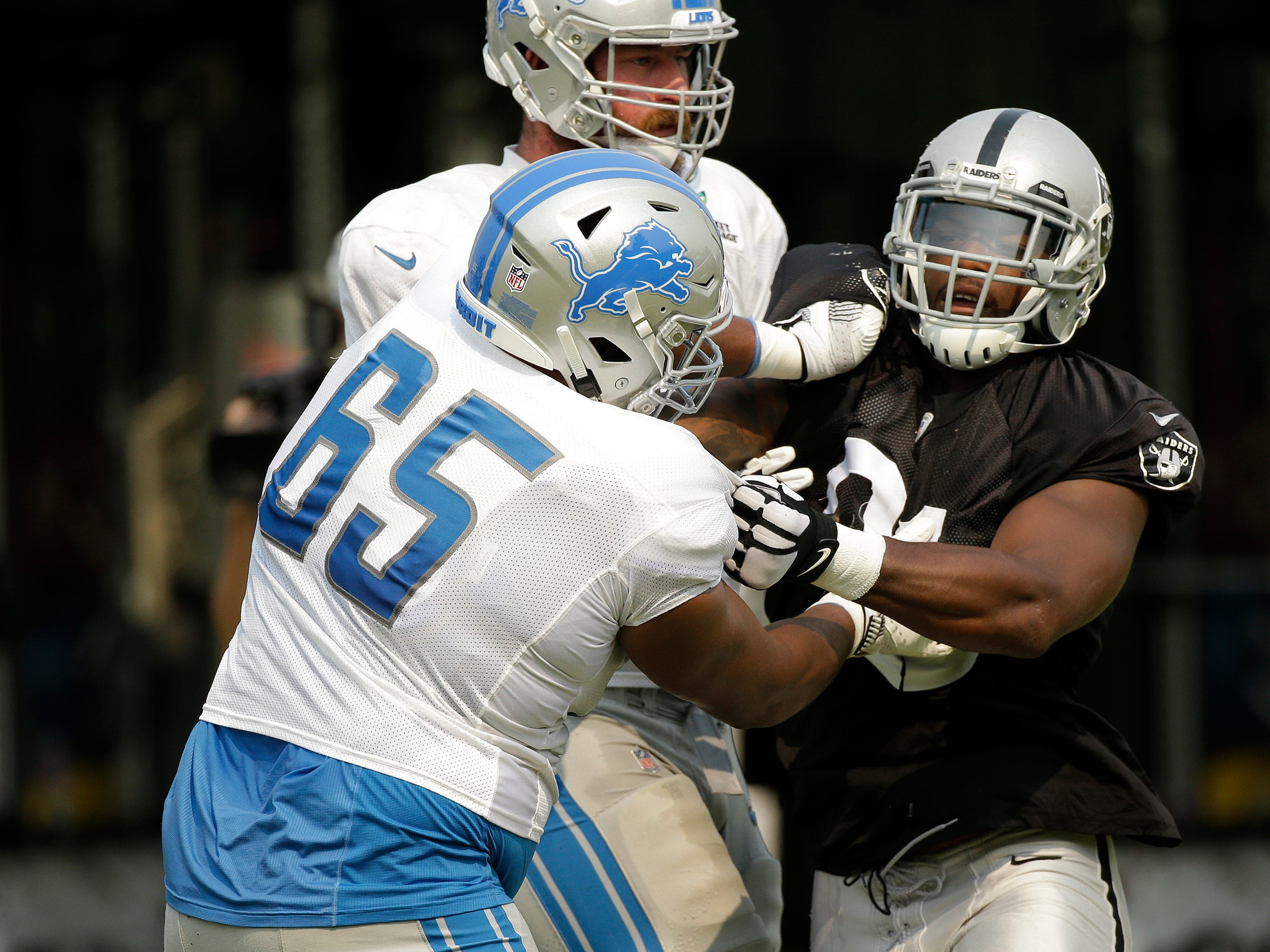 Detroit Lions offensive guard Tyrell Crosby (65) and Oakland Raiders linebacker Shilique Calhoun, right, scrimmage.