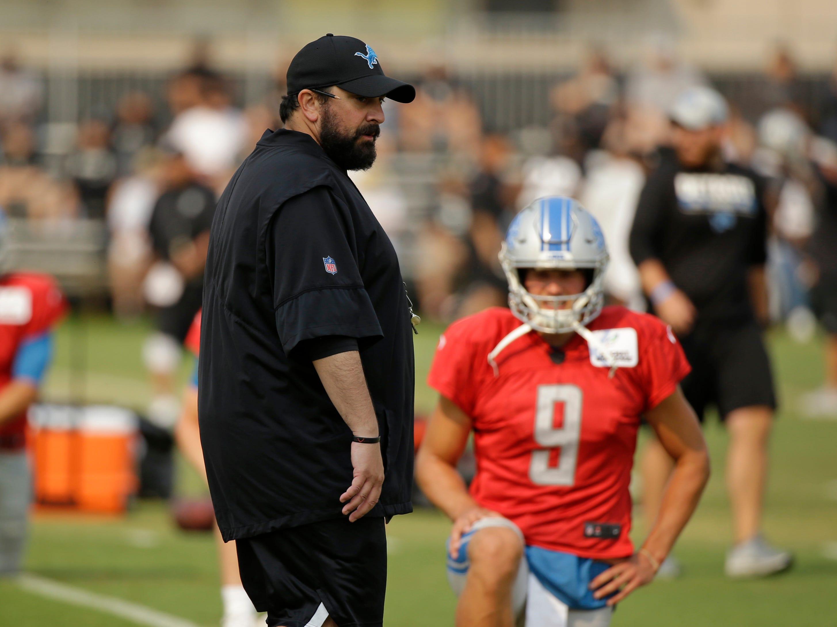 Detroit Lions head coach Matt Patricia watches players stretch as quarterback Matthew Stafford looks on.