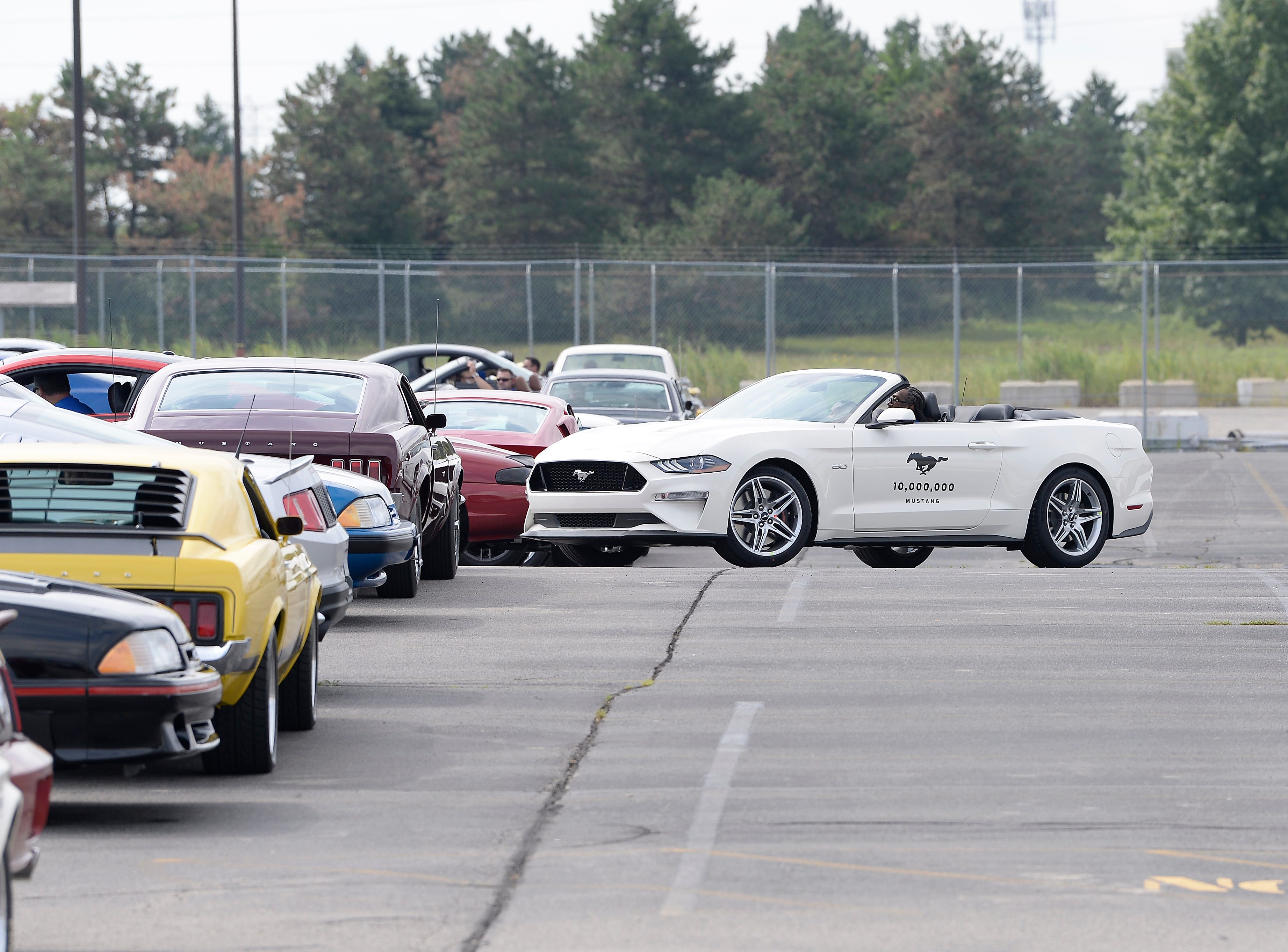 The 10 millionth Mustang enters the gate at the Flat Rock plant to join the other Mustangs to make a formation spelling out 10,000, 000.