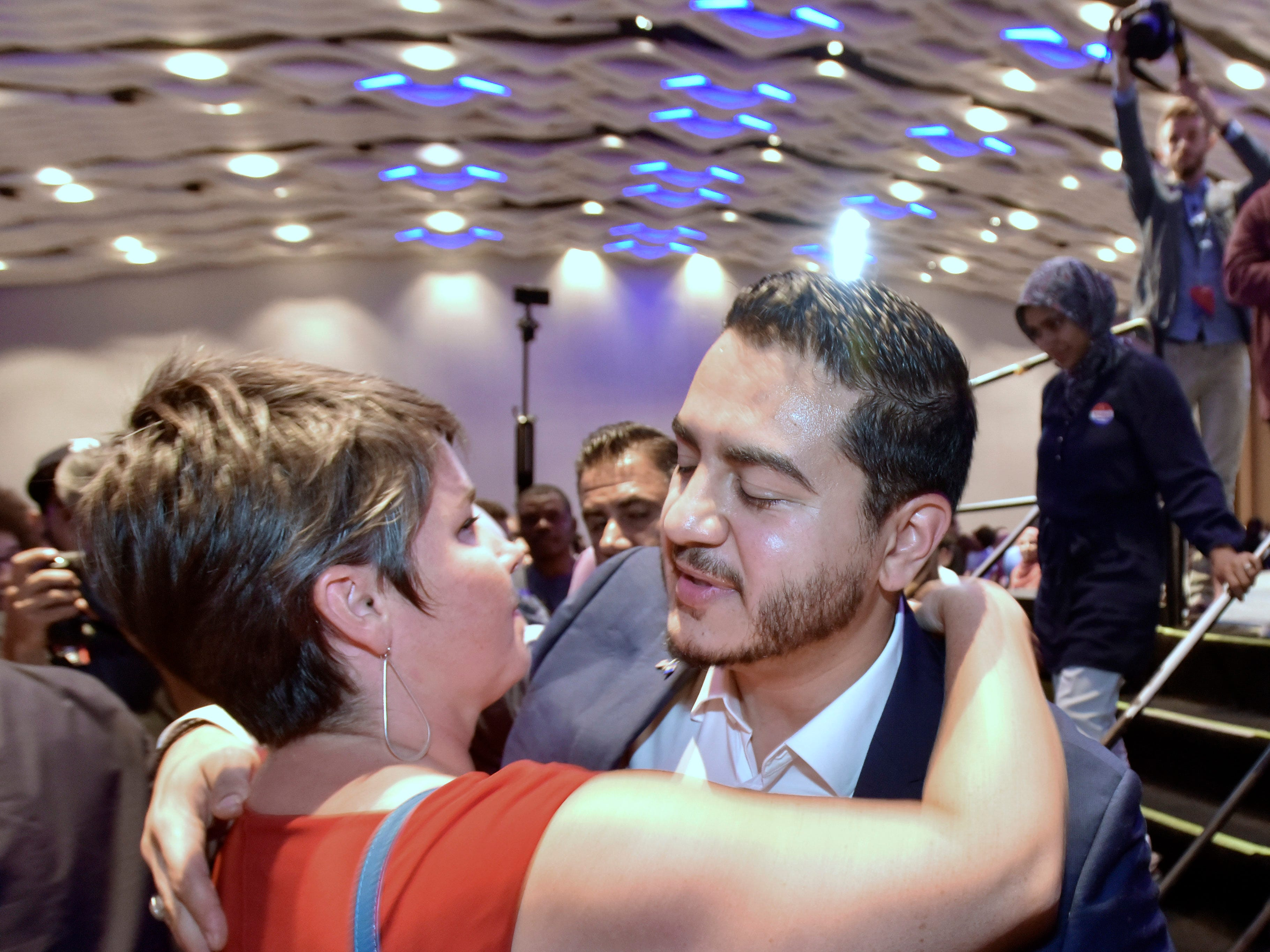 Campaign employee Betsy Coffia, left, of Traverse City, hugs Dr. Abdul El-Sayed after he leaves the stage.