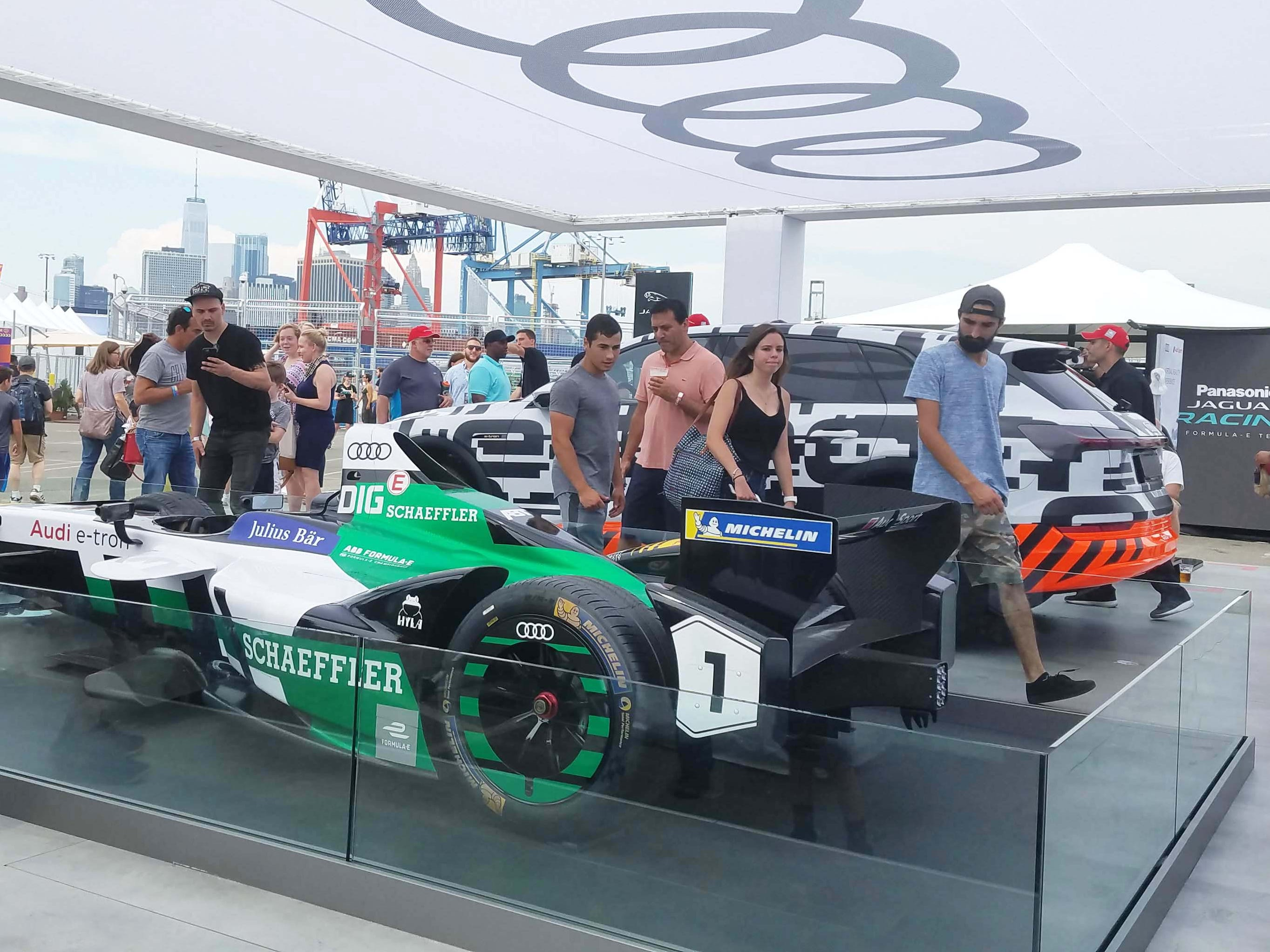 Manufacturers use Formula E to show off their EV tech. Here a fan poses in the fan zone in front of Audi's FE race car — and an Audi e-Trom EV SUV.