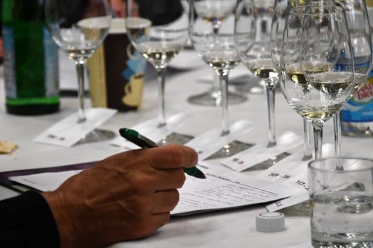 Judges keep track of the paperwork on each wine as they work their way through dry white Michigan wines during the annual Michigan wine competition held at MSU's Kellogg Center on Tuesday, July 31, 2018.  (Dale G.Young/Detroit News) 2018.