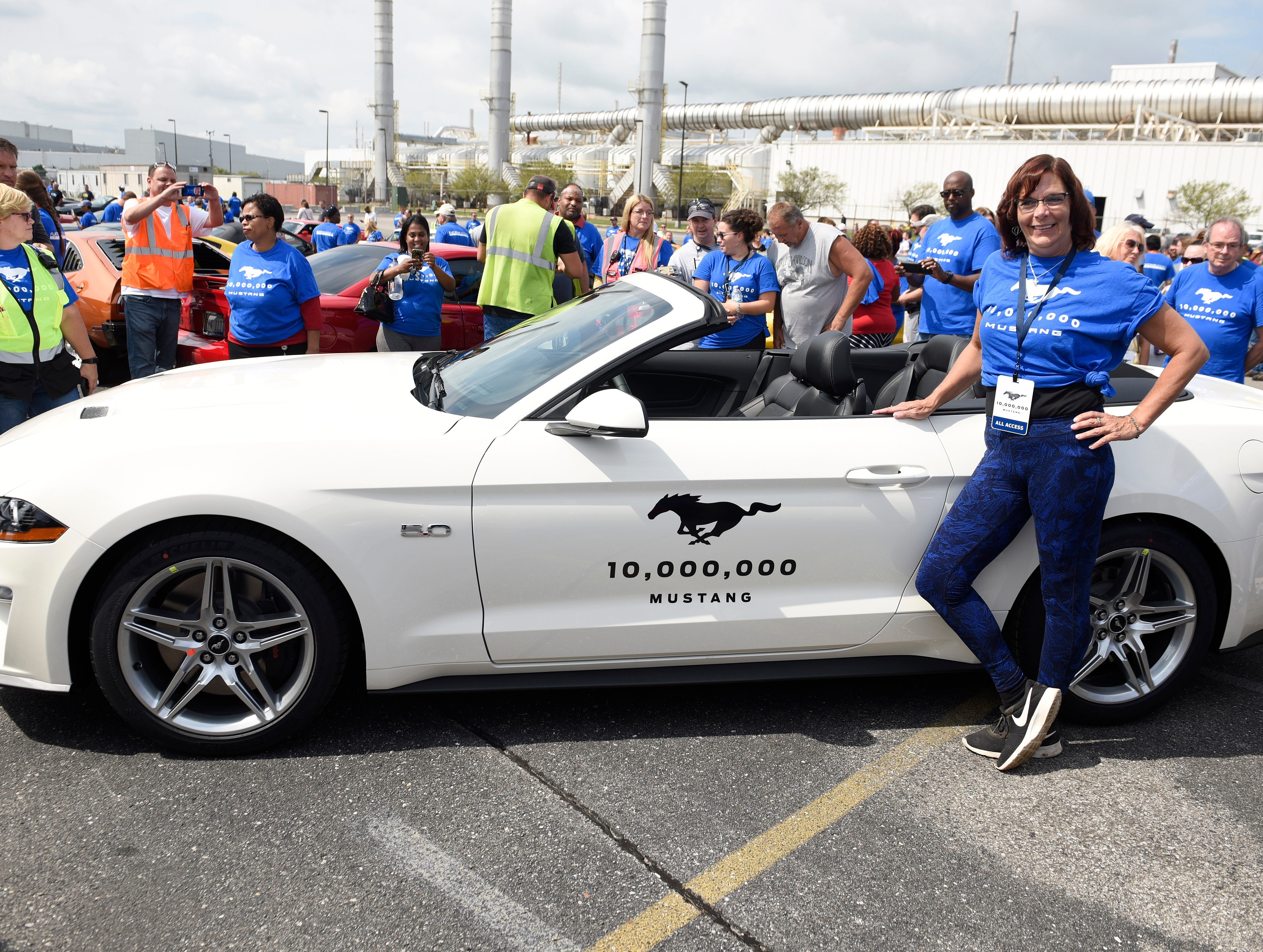 30-year plant employee Susan Spaulding poses with the 10 millionth Mustang during the event.