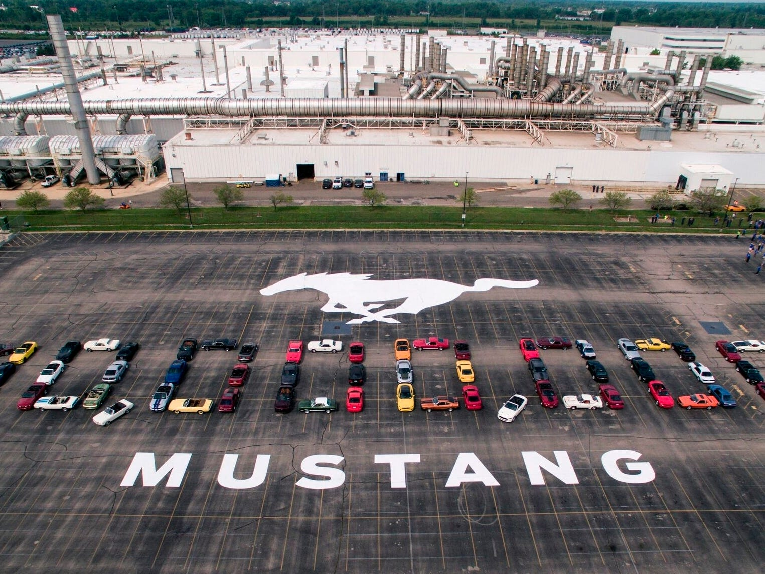 Mustang vehicles are parked to spell out 10,000,000 on a parking lot at the Flat Rock Assembly plant. The commas were represented by the first Mustang produced and the 10 millionth, a 2019 Wimbledon White GT V-8 six-speed manual convertible.