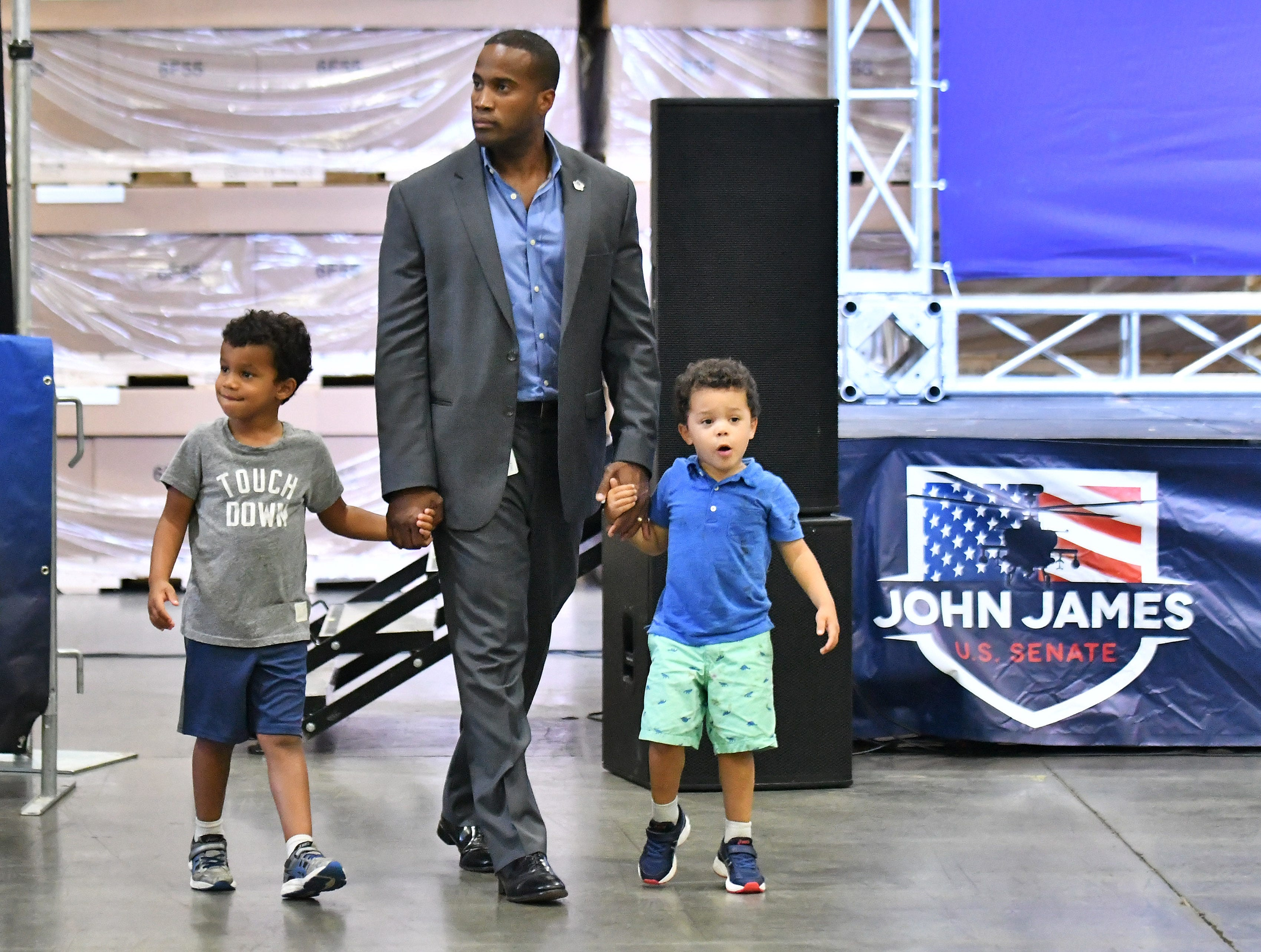 Republican candidate for U.S. Senate John James walk through the venue for his election night party with his sons, John and Hudson at James Group International in Detroit on Aug. 7, 2018.