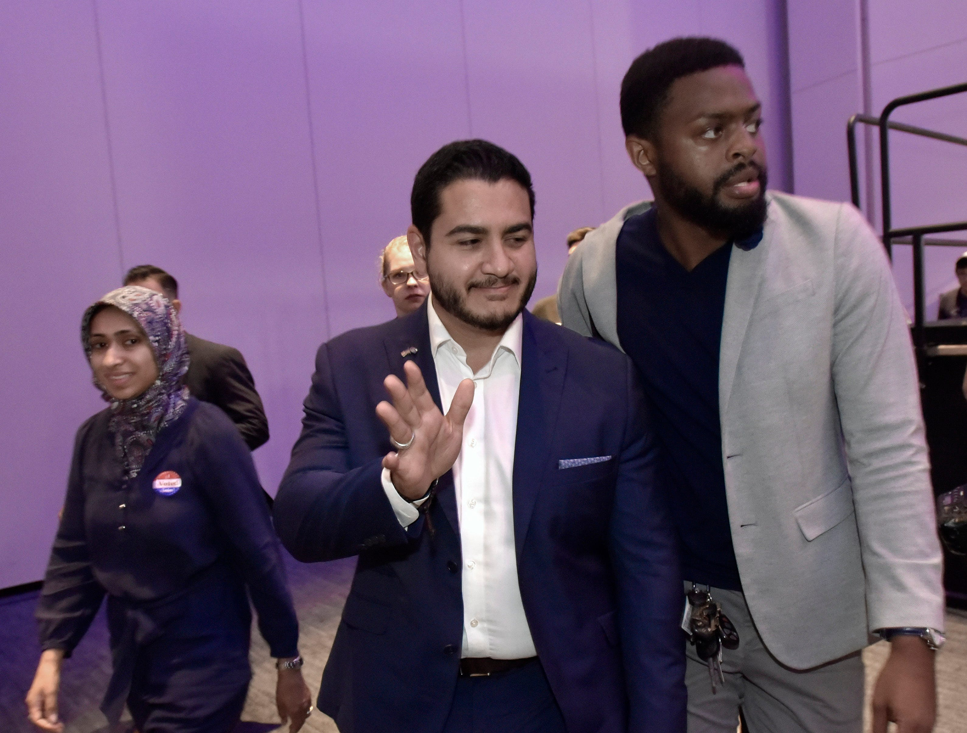 Dr. Abdul El-Sayed, center, is escorted from the stage as his wife, Dr. Sarah Jukaku, MD, left, stays close.