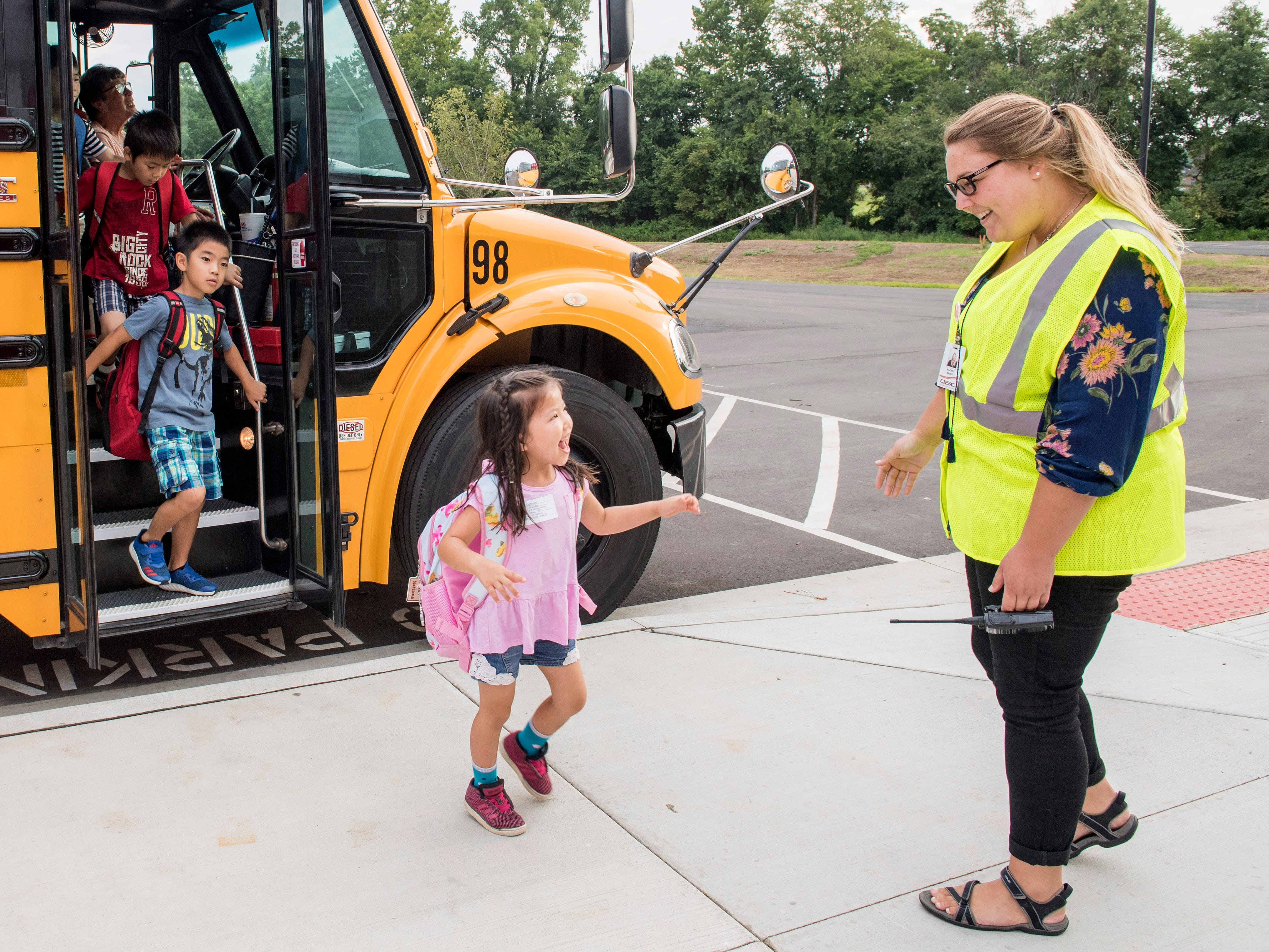 McCutchanville Elementary School counselor Rachel Bauer greets students while exiting the buses on the first day of school Wednesday, August 8, 2018.