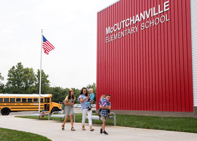 Ashley Lee, middle, takes a photo of second grader Jackson Lee, front, carrying his sister Annaston up the sidewalk while older sister Madison Lee, fifth grade,  trails behind on the first day of school at McCutchanville Elementary Wednesday, August 8, 2018.