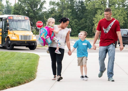 Kindergartener Asher Buttrum, middle, is ushered along the sidewalk at new McCutchanville Elementary School by sister Kenna, mom Kelly and dad Tanner on the first day of school Wednesday, August 8, 2018.