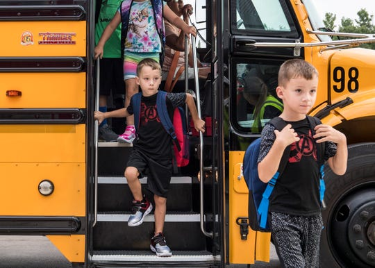 Students race off the bus at the new McCutchanville Elementary school for the first day of school Wednesday, August 8, 2018.