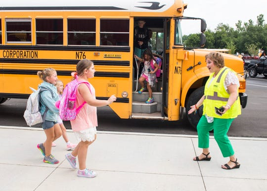 McCutchanville Elementary school principal Lisa Shanks enthusiastically greets students as they arrive for the first day of school Wednesday, August 8, 2018.
