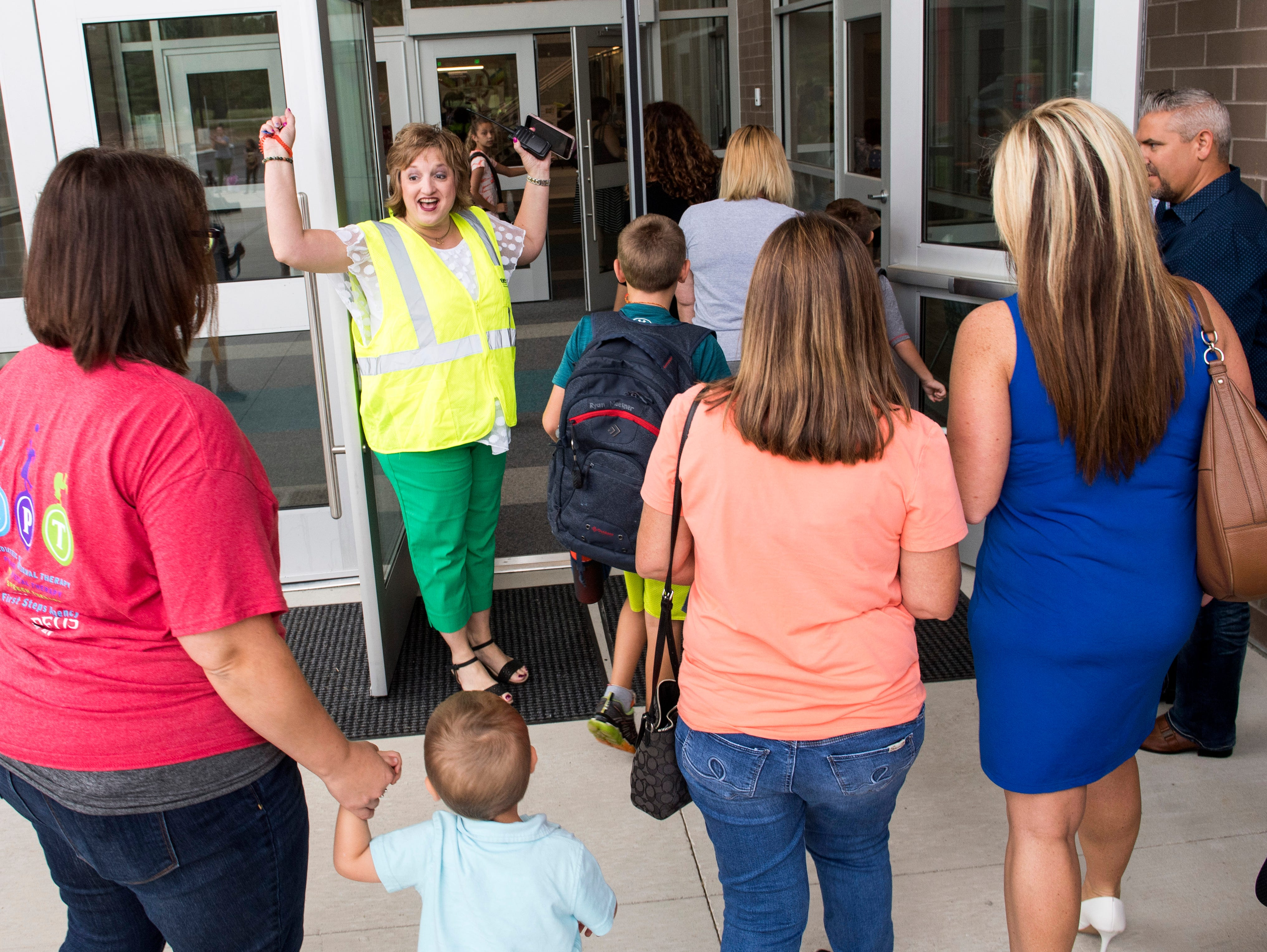 McCutchanville Elementary school principal Lisa Shanks, middle, opens the doors for the first time with a cheer while students arrive for the first day of school Wednesday, August 8, 2018.
