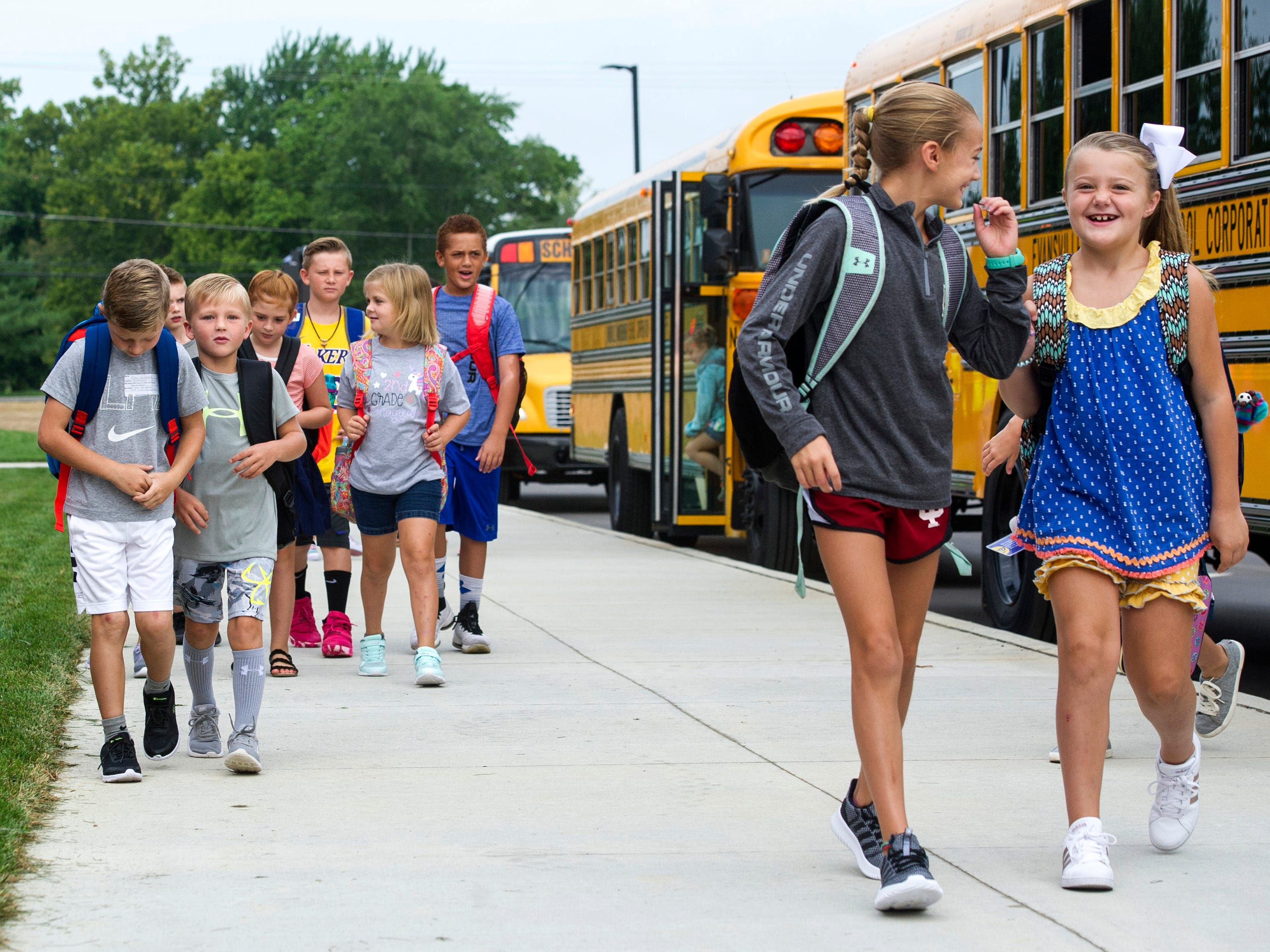 Students race off the buses at the new McCutchanville Elementary school for the first day of school Wednesday, August 8, 2018.