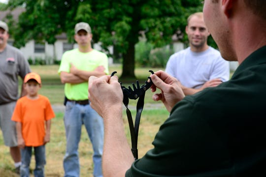 Jaron Beck, outdoor skills specialist with the Ohio Division of Wildlife, shows a device for catching frogs during a workshop on Tuesday night.