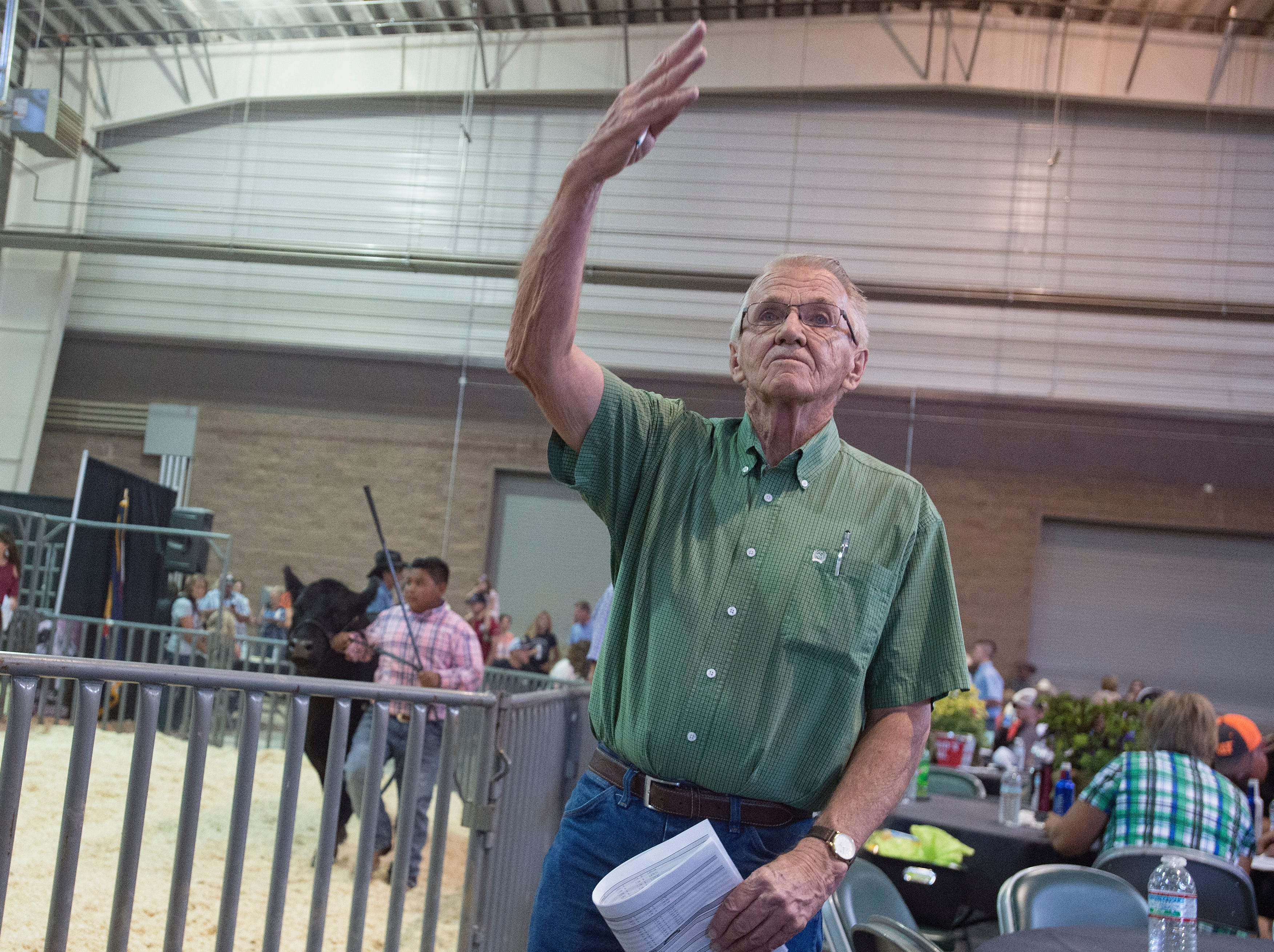 Don Cook calls out bids during the Larimer County Fair Youth Livestock Sale at The Ranch in Loveland on Wednesday, August 8, 2018.