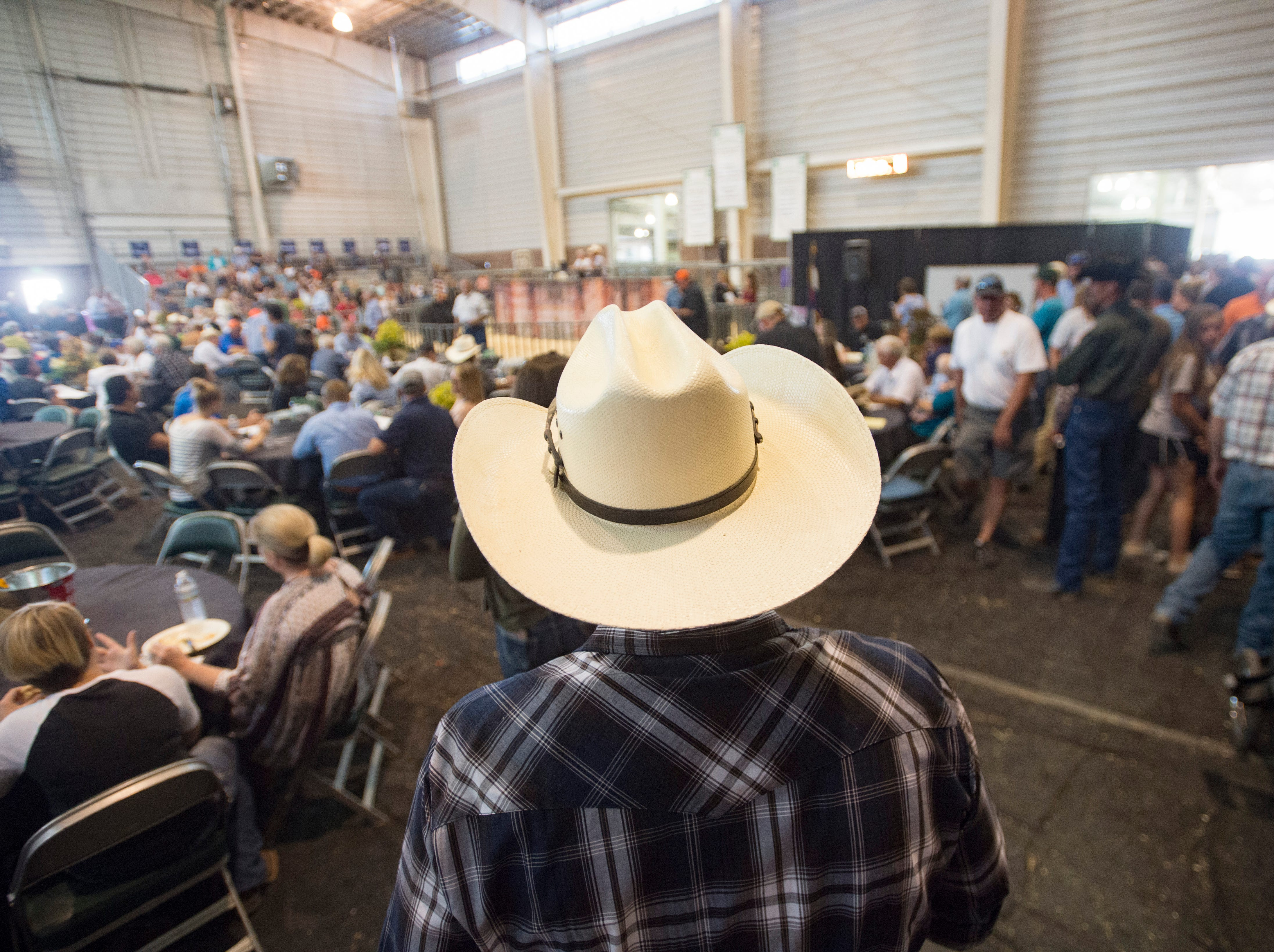 Rusty Dailey wears his cowboy hat while he watches bidding at the Larimer County Fair Youth Livestock Sale at The Ranch in Loveland on Wednesday, August 8, 2018.