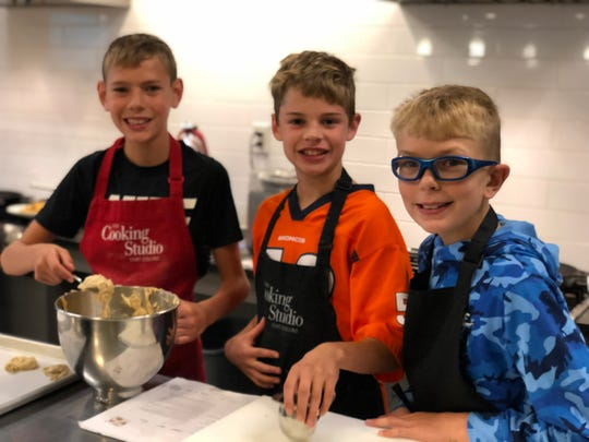 A group of students learn to cook at The Cooking Studio.