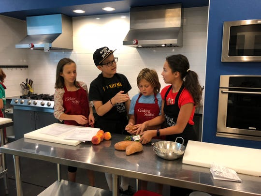 A group of students discuss what to cook at The Cooking Studio.
