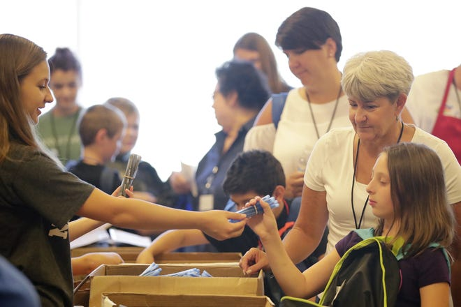 Volunteer Lainey Simonson hands out pens to children at the Back-to-School Store at University of Wisconsin-Green Bay on Wednesday in Green Bay.