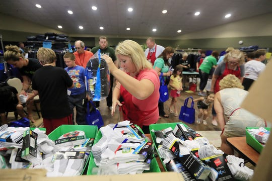 Volunteers pass out school supplies at the Back to School store at University of Wisconsin-Green Bay on Wednesday in Green Bay.