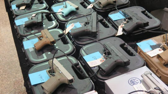 In this file photo, an array of handguns are on display at a gun show.