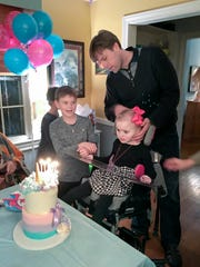 Erik Ching helps Halle at a birthday party as son Anders looks on.