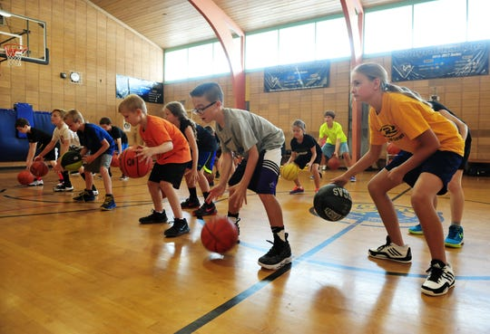 Kids practice dribbling at the Reece Gliko Baskeball Camp, Wednesday.