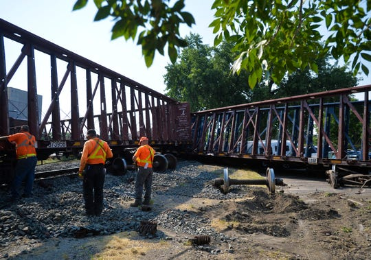 BNSF rail workers investigate a train derailment that occured on the tracks between the Great Falls Police Department and the Great Falls Tribune building on Wednesday afternoon.  Numerous cars in the police department parking lot were damaged by train cars.