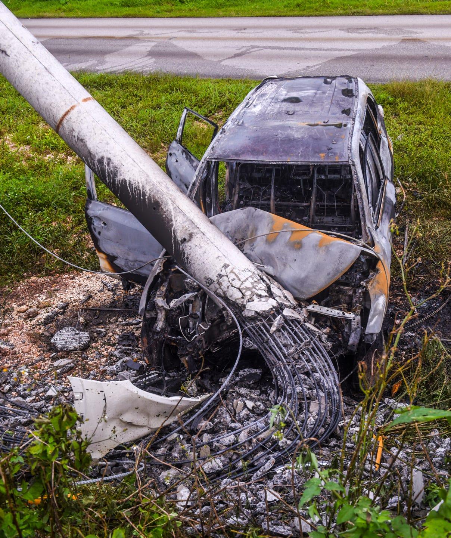 Car burns after crashing into power pole