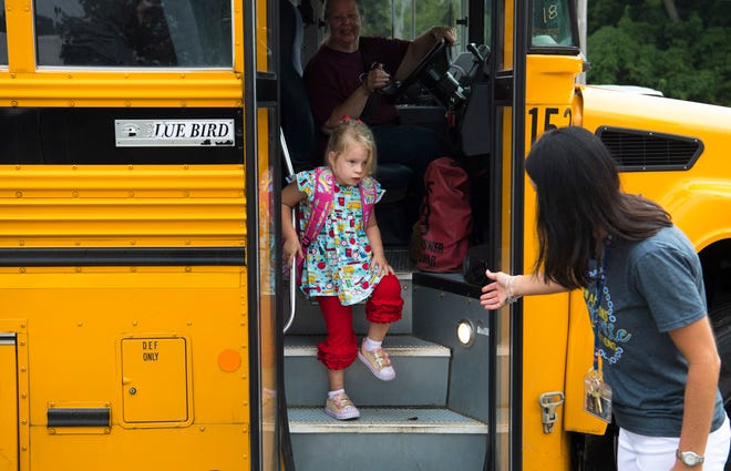 First-grader Olivia Bailey, 6, eases down the school bus steps as she is greeted by Principal Sarah Estabrook on the first day of school at Spottsville Elementary School Wednesday morning.