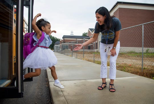 Kindergartener Galilea Guivas, 5, leaps from the school bus to embrace Principal Sarah Estabrook on her first day of school at Spottsville Elementary School Wednesday morning.