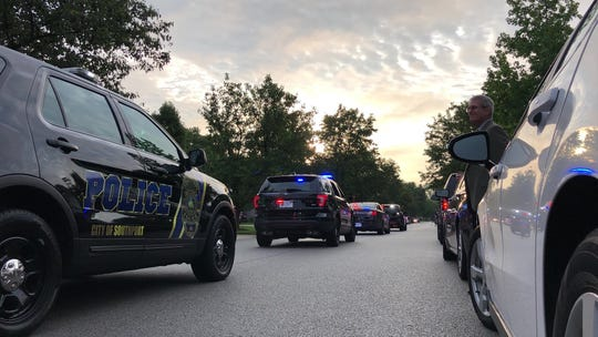 Police escort the son of slain Southport Lt. Aaron Allan to school on Wednesday, Aug. 8, 2018.
