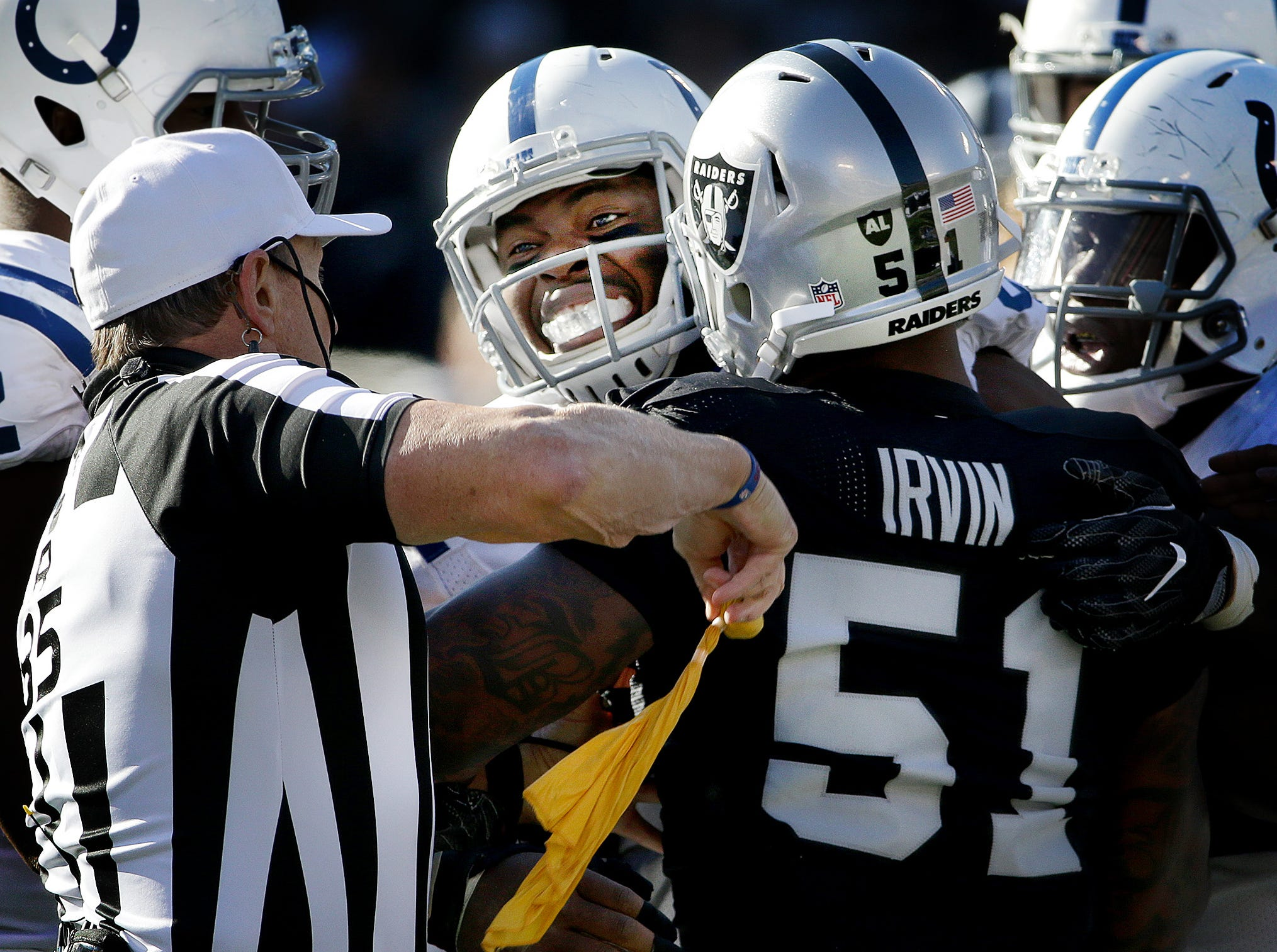 Indianapolis Colts tight end Dwayne Allen (83) gets into a shoving match with Oakland Raiders outside linebacker Bruce Irvin (51) as NFL referee Ed Hochuli (85) flagged the two for unsportsmanlike conduct at Oakland Alameda Coliseum in Oakland, Calif. Saturday, December 24, 2016.