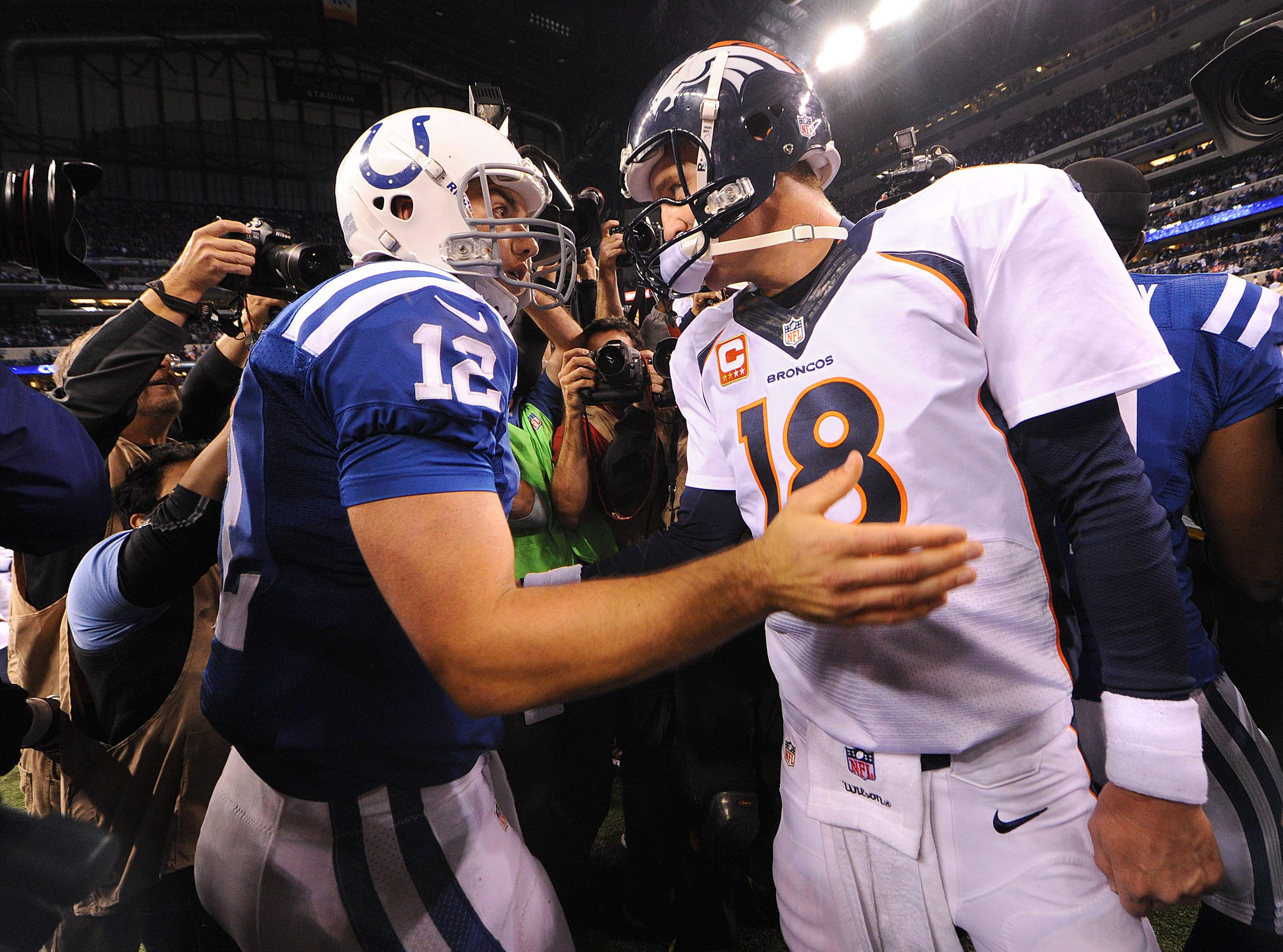 Indianapolis Colts' Andrew Luck (12) and Denver Broncos' Peyton Manning (18) meet on the field after the Bronco's 39-33 loss to Colts on October 20, 2013, at Lucas Oil Stadium.