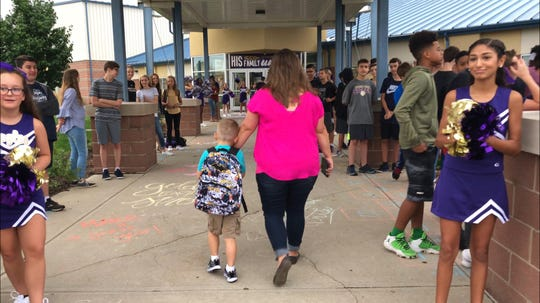 Aaron Allan Jr., son of slain Southport Lt. Aaron Allan, and his mother Stacy Allan enter the school for the start of first grade.