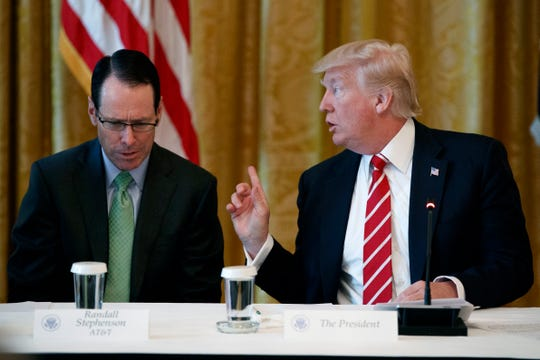"In this June 22, 2017, file photo, AT&T CEO Randall Stephenson, left, listens as President Donald Trump speaks during the ""American Leadership in Emerging Technology"" event in the East Room of the White House in Washington. AT&T workers backed by the Communications Workers of America say Stephenson has failed in his promises to add jobs since Trump signed a tax overhaul into law in December 2017."