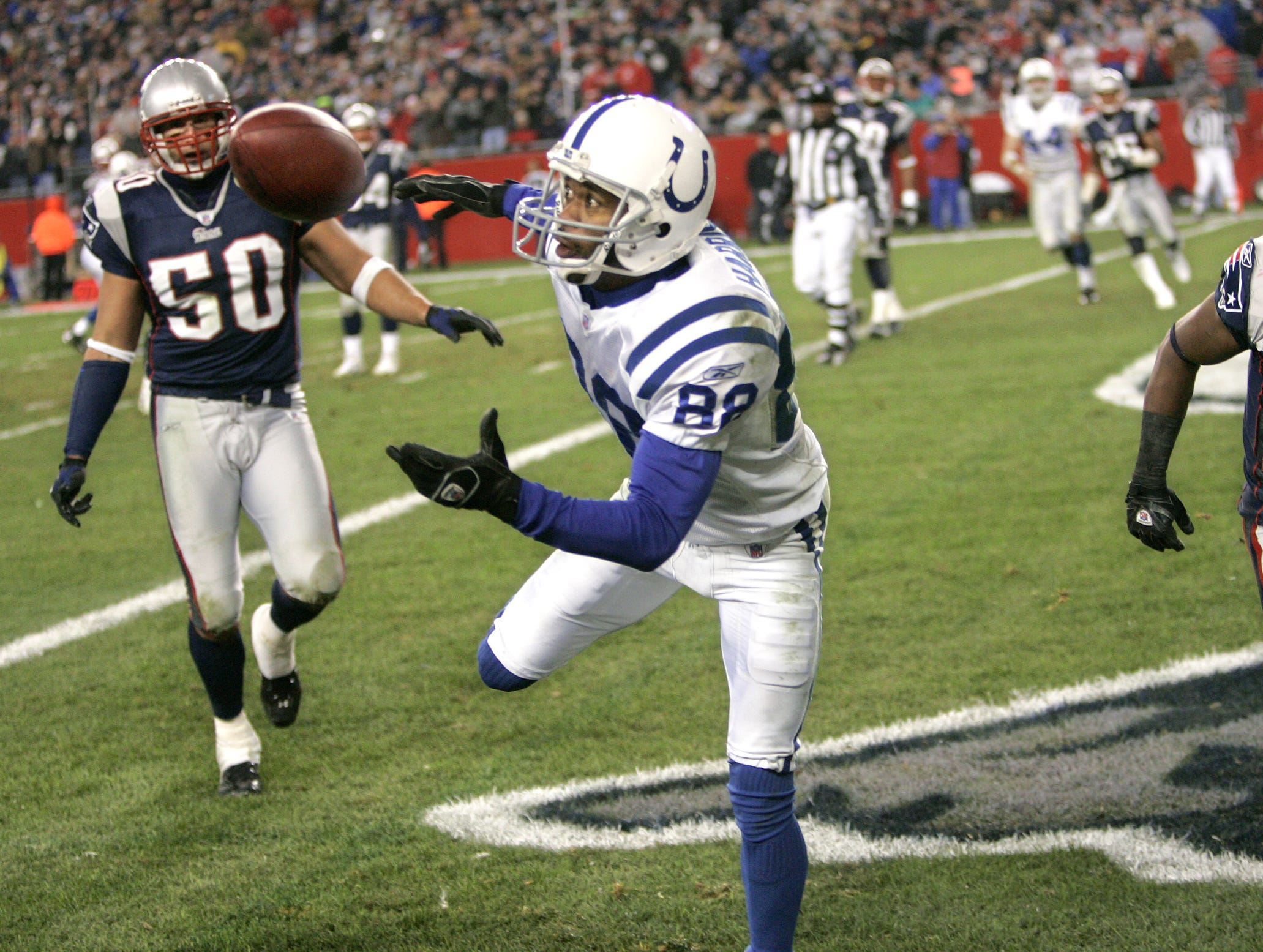 Indianapolis Colts Marvin Harrison keeps his concentration on the ball as he splits Patriot defenders Mike Vrabel and Ellis Hobbs to pull in a touchdown pass in the third quarter of their game Sunday, Nov 11, 2006.