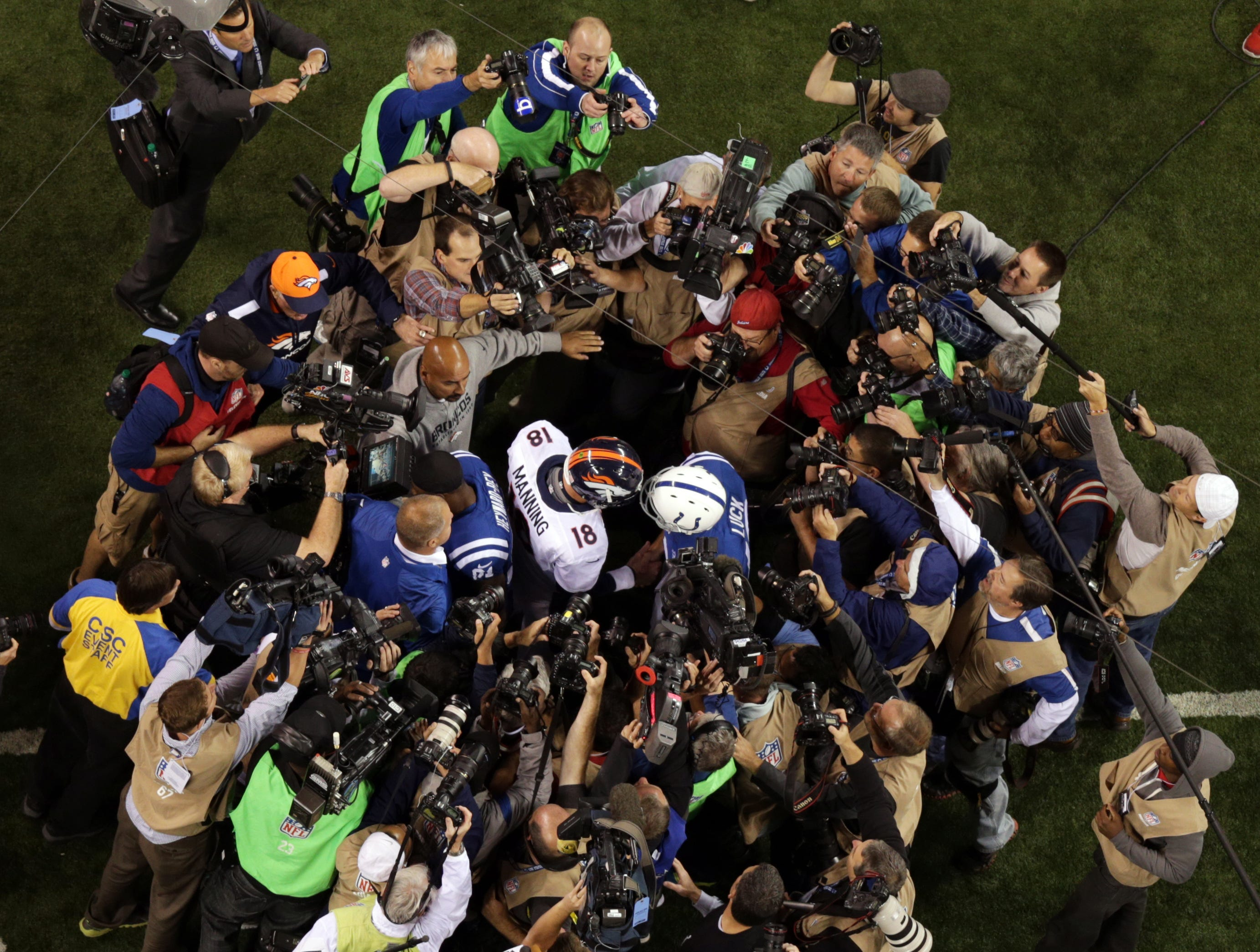 Andrew Luck and Peyton Manning are surrounded by photographers as they met following their game October 20, 2013 at Lucas Oil Stadium.  Indianapolis won 39-33.