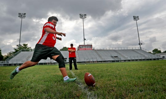 Lester practices kicking at Emmerich Manual High School, Monday, July 31, 2018, as special teams and receiving coach Jerod Kienitz looks on.  Lester moved to Indianapolis when he was 15 years old and is set to graduate from Manual in 2019.  Lester, an undocumented immigrant from Honduras, dreams of going to college.  He hopes that football will help him pay for that dream.