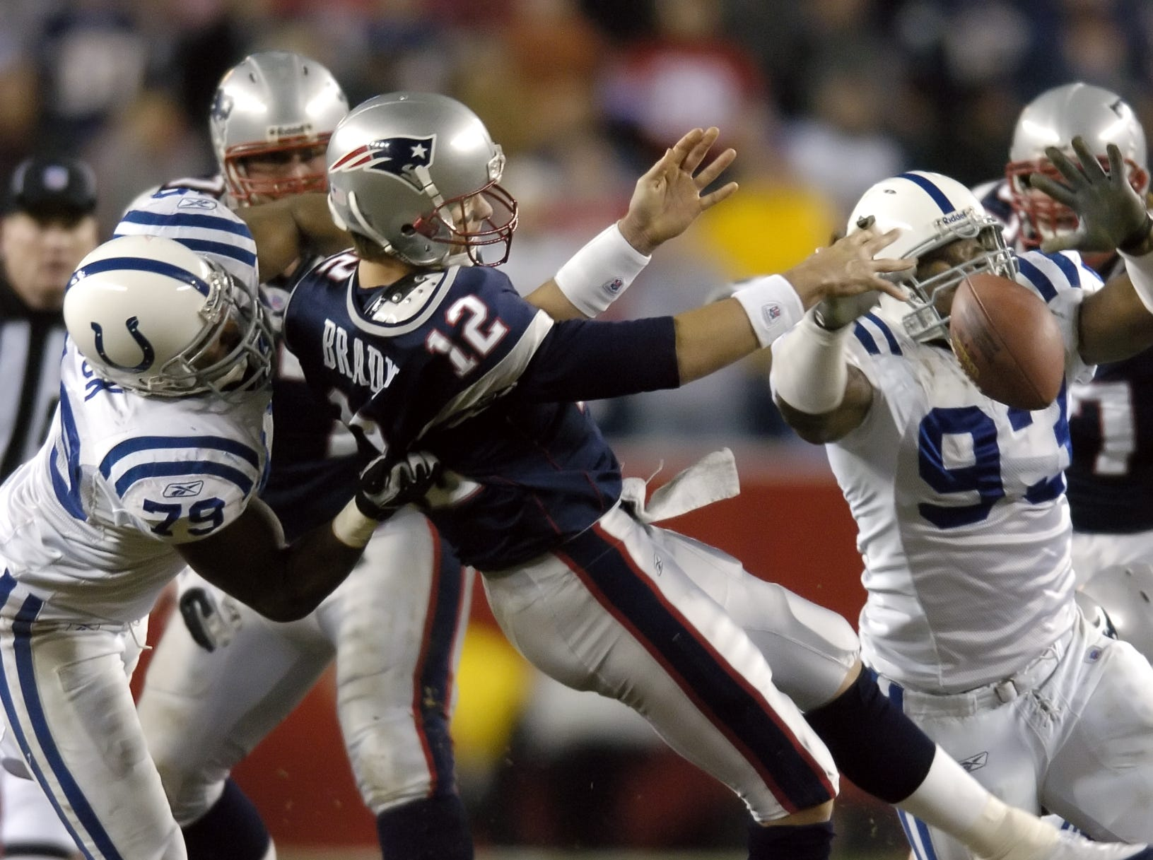 New England Patriots quarterback Tom Brady fumbles the ball under pressure from Indianapolis Colts Raheem Brock and Dwight Freeney at Gillette Stadium in Foxboro MA. on Nov 7, 2005.
