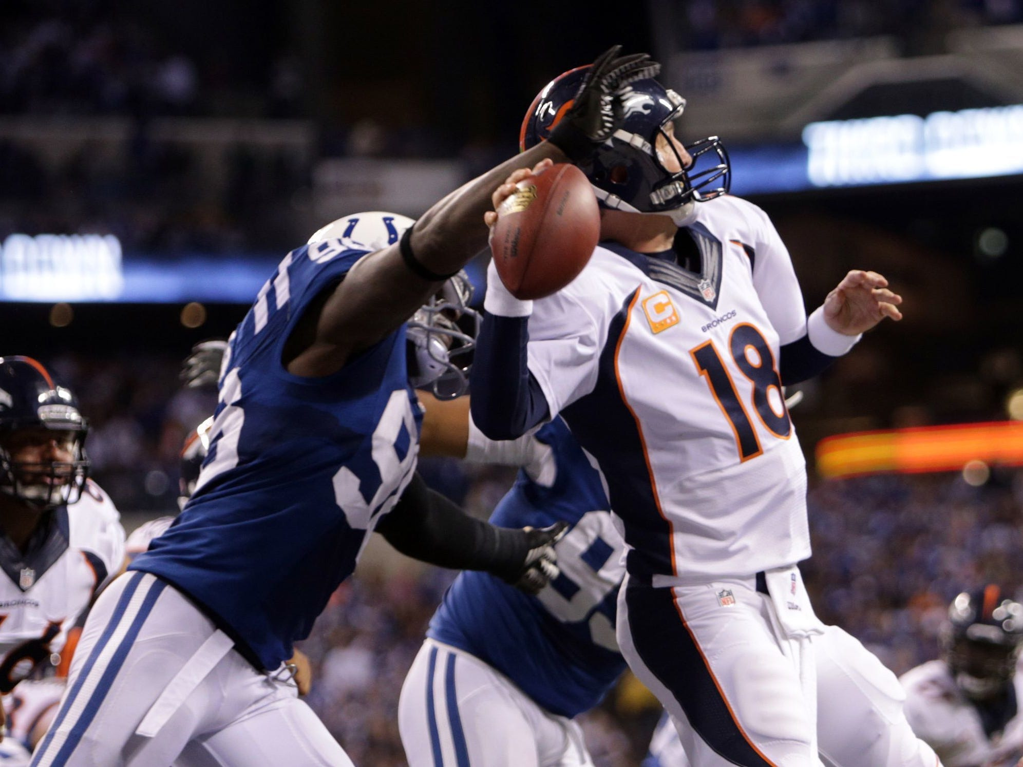 Denver Broncos quarterback Peyton Manning is hit from behind by former teammate Robert Mathis during their game at Lucas Oil Stadium on October 20, 2013.