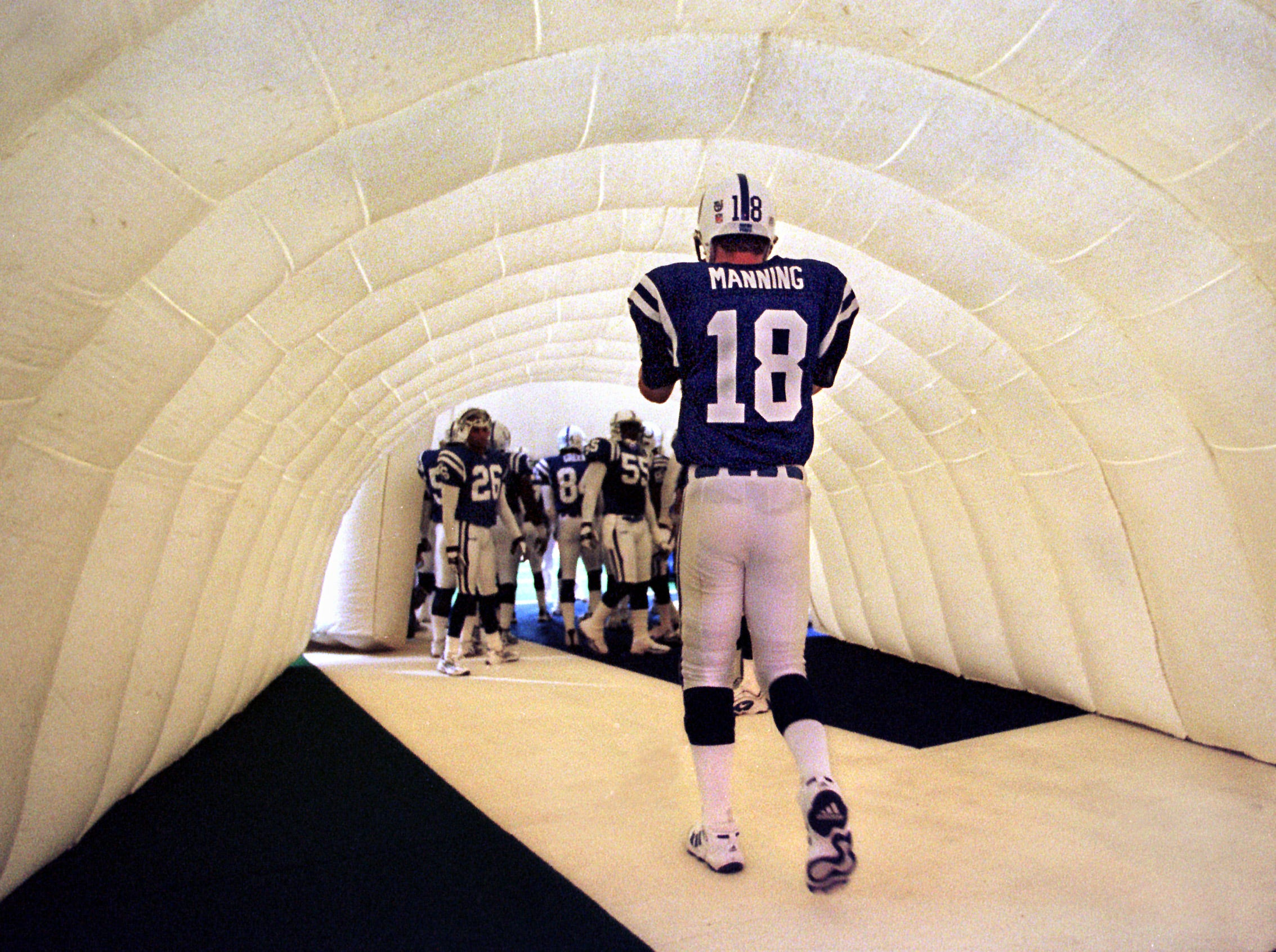 Indianapolis Colts quarterback Peyton Manning walks through the giant football helmet before being introduced before the start of their game against the New England Patriots on Dec 12, 1999