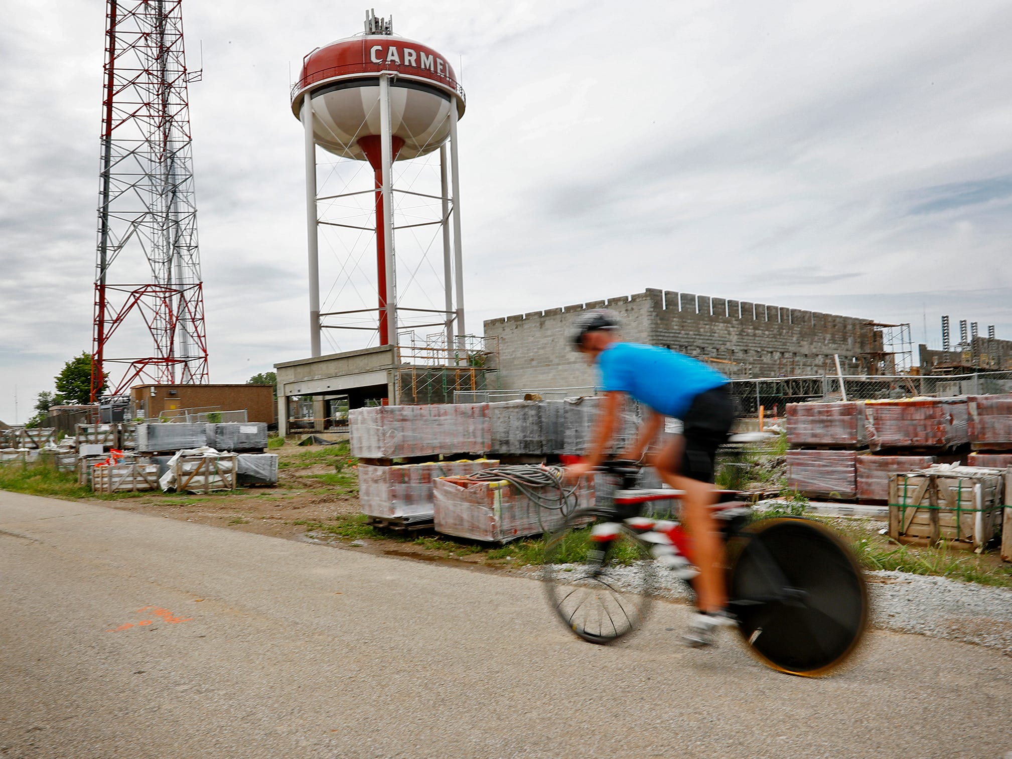 A cyclist travels south on the Monon Trail, passing the future home of Merchants Bank, in Midtown Carmel, Tuesday, Aug. 7, 2018.