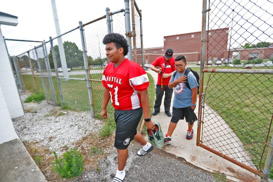 Lester, left, heads to the football field for practice at Emmerich Manual High School, Monday, July 31, 2018.  He moved to Indianapolis when he was 15 years old and is set to graduate from Manual in 2019.  Lester, an undocumented immigrant from Honduras, dreams of going to college.  He hopes that football will help him pay for that dream.
