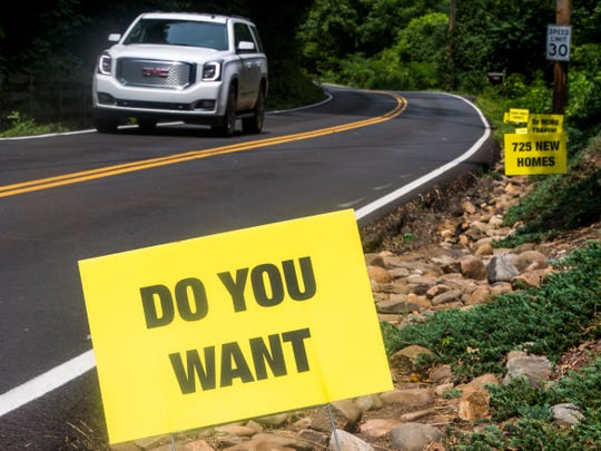"""Signs asking local residents """"Do you want 725 more homes, 5x more traffic on this road? Your voice counts Aug. 9 MPC meeting."""" line Tooles Bend Road off Northshore Drive in Knoxville on Aug. 8, 2018."""